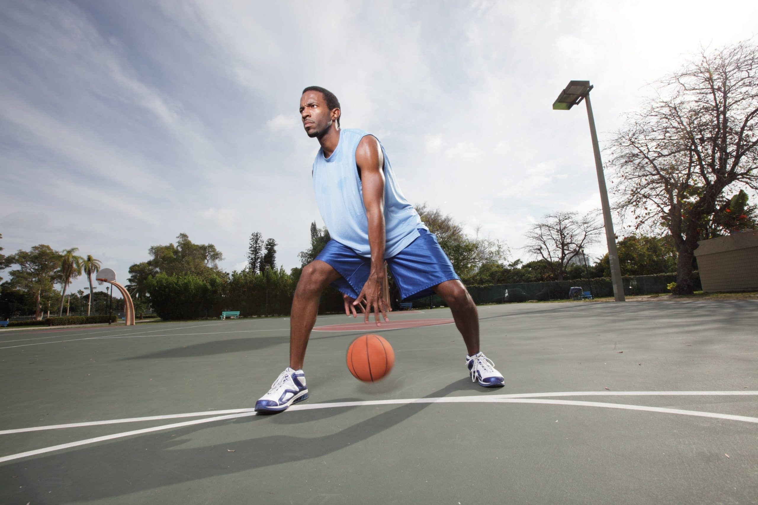 young man playing basketball outside